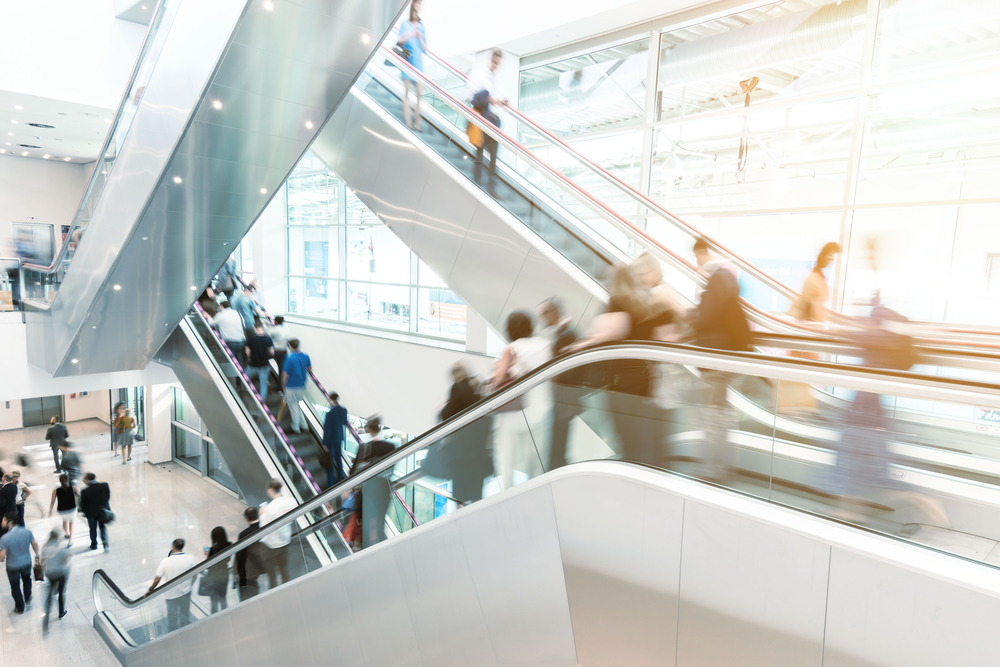 countless people on an escalator going to and from shops in a mall.